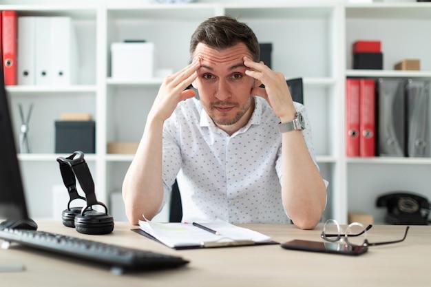 Een jonge man zit aan een tafel op kantoor en houdt zijn handen achter zijn hoofd.