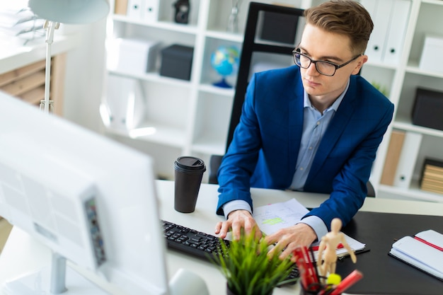 Een jonge man zit aan een tafel op kantoor en werkt met documenten en een computer.