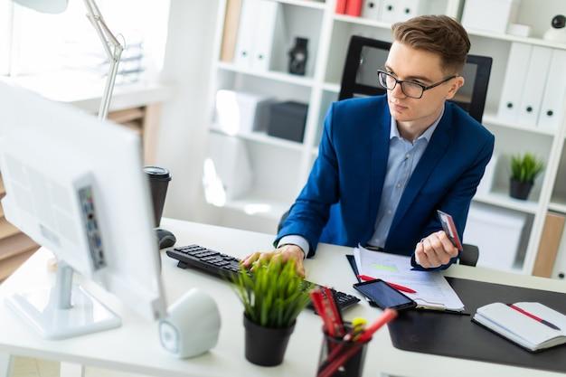 Een jonge man zit aan een tafel op kantoor, houdt een bankpas in zijn hand en typt op een computer.