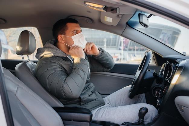 Een jonge man zit achter het stuur en draagt een masker voor persoonlijke veiligheid tijdens het rijden tijdens een pandemie en coronavirus. epidemie.