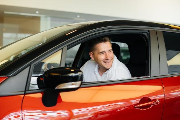 Een jonge man zit in de cabine van een nieuwe auto en test hem. een auto kopen.