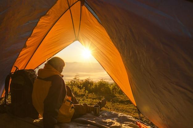 Een jonge man zit in de tent, kijkend naar het berglandschap in de winter