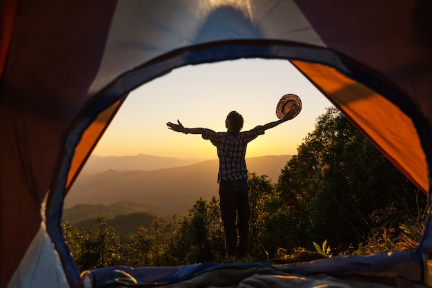 Een jonge man zit in de tent met het nemen van foto met een mobiele telefoon