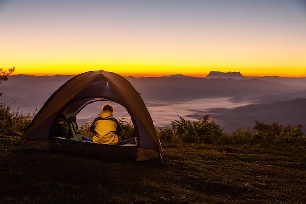 Een jonge man zit in de tent met kijken naar het berglandschap in de winter