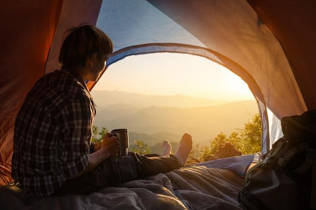 Een jonge man zit in de tent met koffiekopje te houden