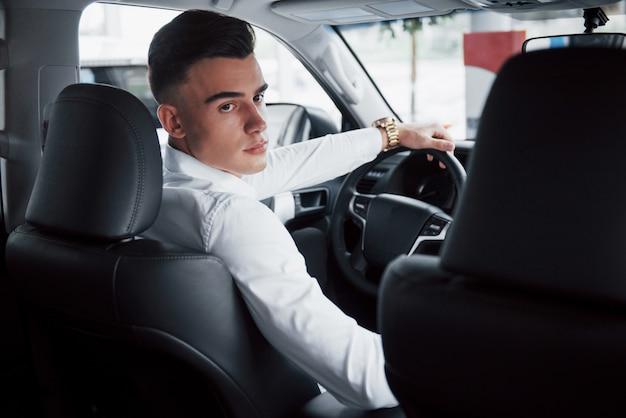 Een jonge man zit in een nieuw gekochte auto achter het stuur, een succesvolle aankoop.