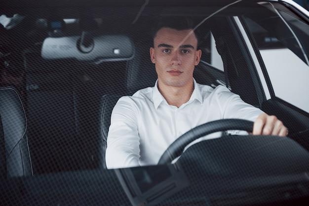 Een jonge man zit in een pas gekochte auto met zijn handen op een roer