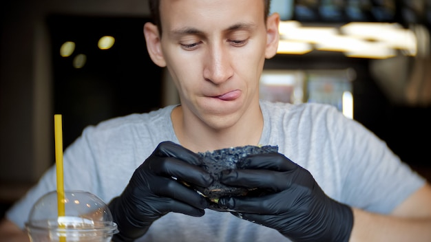 Een jonge man zit in een restaurant en kijkt aandachtig naar de burger die hij in zijn handen houdt.