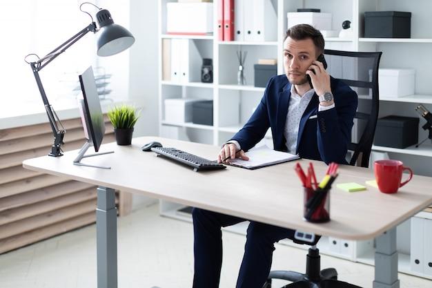 Een jonge man zit in het kantoor aan de tafel, aan de telefoon te praten en een potlood in zijn hand te houden. de jonge man heeft documenten.
