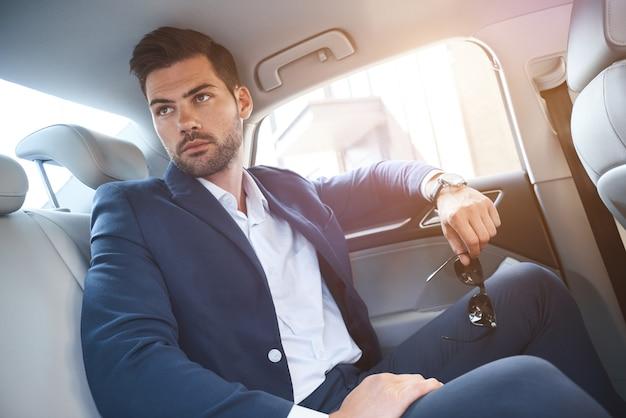 Een jonge man zit op de achterbank van auto's en kijkt uit het raam
