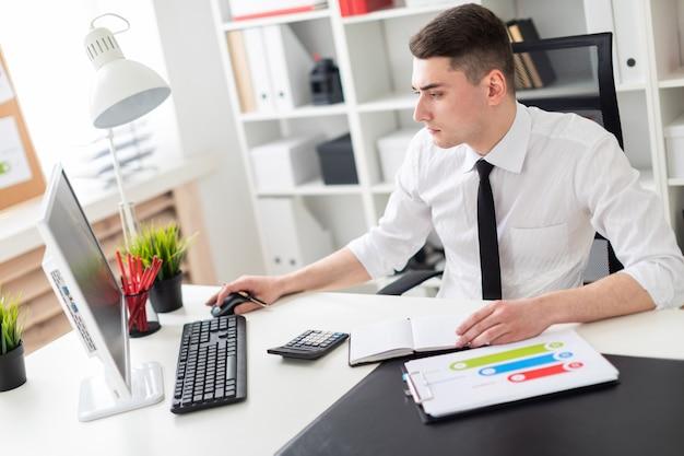 Een jonge man zit op een computer bureau op kantoor en werkt met documenten.
