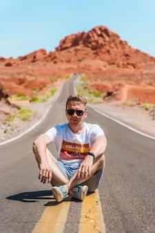 Een jonge man zit op een schilderachtige weg in valley of fire nevada