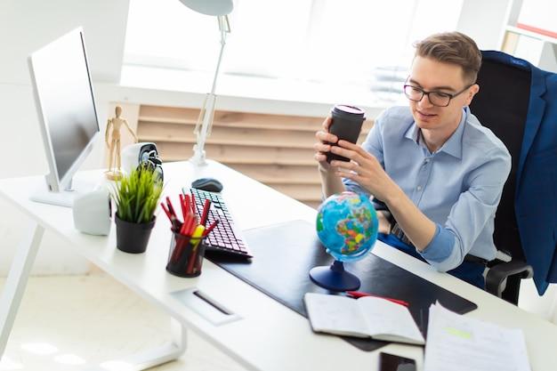 Een jonge man zit op kantoor achter een computerbureau en houdt een glas koffie in zijn hand. een jonge man staat voor een wereldbol.