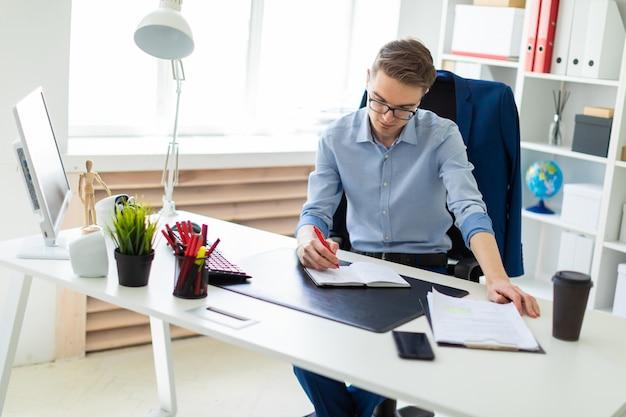 Een jonge man zit op kantoor achter een computerbureau en schrijft in een notitieblok.