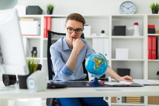 Een jonge man zit op kantoor achter een computerbureau en voor hem staat een wereldbol.