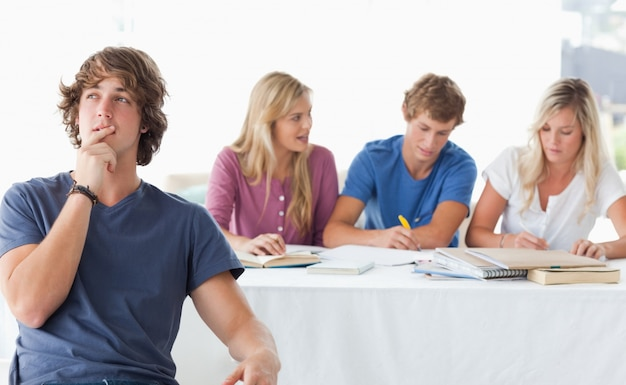 Een jonge man zit voor zijn werkende klasgenoten en denkt