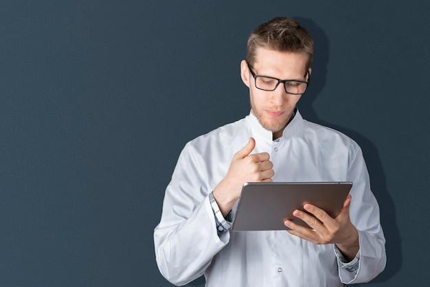Een jonge mannelijke arts die een digitale tablet vasthoudt die zich in de buurt van de kleurenmuur bevindt