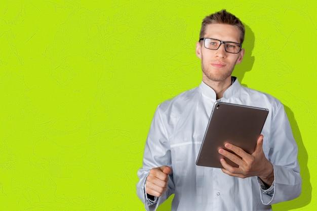 Een jonge mannelijke arts die een digitale tablet vasthoudt die zich in de buurt van de kleurenmuur bevindt Premium Foto