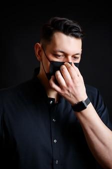 Een jonge mannelijke arts in een zwart chirurgisch pak zet een zwart masker op ter bescherming tegen het virus. geïsoleerd op zwarte achtergrond