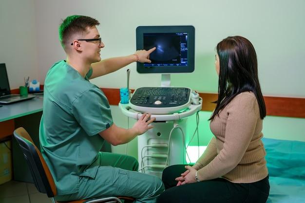 Een jonge mannelijke arts toont de patiënt een echografie van de buikholte. dokter legt een vrouwenanalyse uit. vrolijke mannelijke medicus met speciale apparatuur.