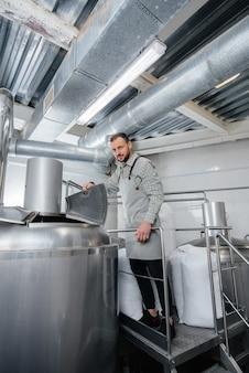 Een jonge mannelijke brouwer giet mout voor bier in een container. een kleine ambachtelijke brouwerij.