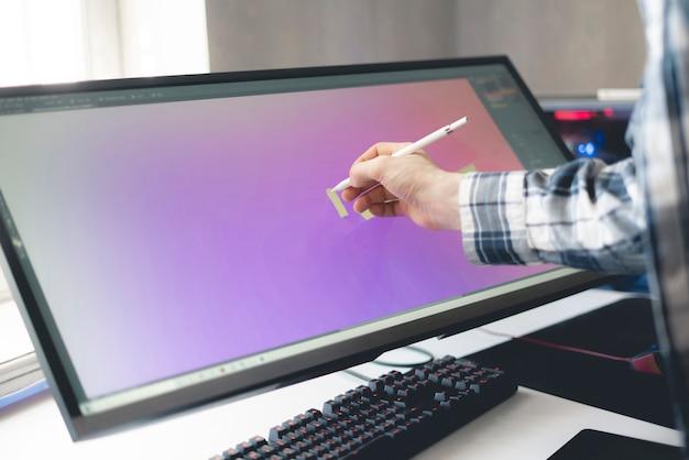 Een jonge mannelijke digitale kunstenaar die verf trekt op de computerschermmonitor in de studio