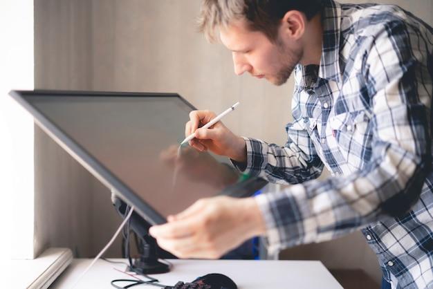 Een jonge mannelijke digitale kunstenaar verf puttend uit de computerschermmonitor in de studio
