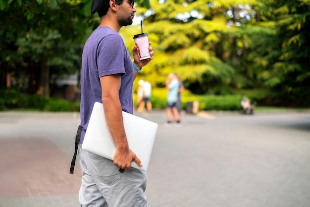 Een jonge mannelijke persoon die de laptop in de stad draagt