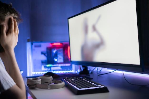Een jonge mannelijke persoon die voor het scherm zit en 's nachts naar de horrorfilm kijkt enge emoties