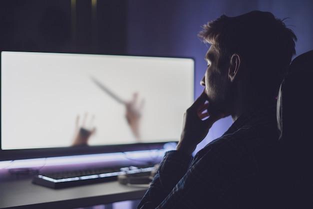 Een jonge mannelijke persoon zit voor het scherm en kijkt 's nachts naar de horrorfilm, enge emoties Premium Foto