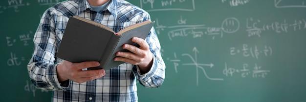 Een jonge mannelijke professor aan de universiteit met een boek in de klas