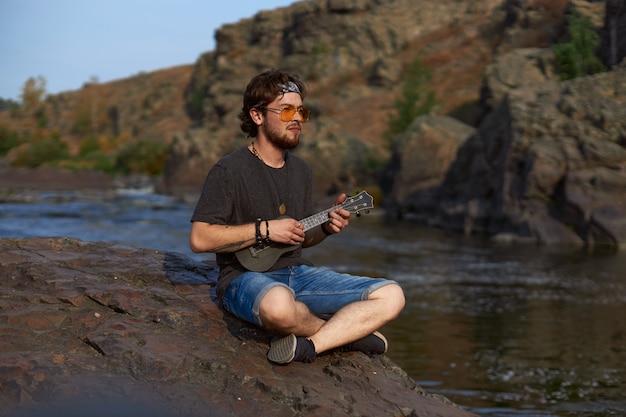 Een jonge mannelijke reiziger zit op een rots bij een bergrivier en speelt de ukelele het concept van jeugd...
