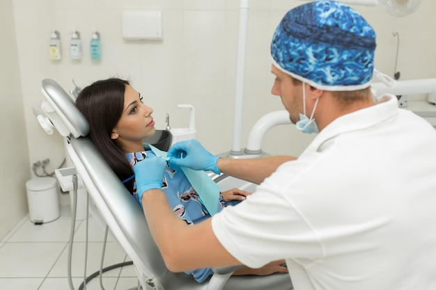 Een jonge mannelijke tandarts en een gelukkige vrouwelijke patiënt. tandarts kantoor levensstijl scène. dokter praktijk. gezondheidszorg voor patiënten