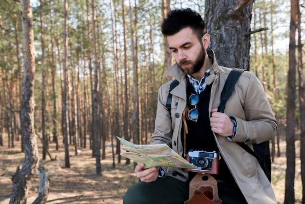 Een jonge mannelijke toerist die de kaart in het bos leest