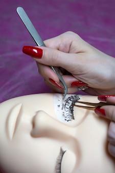 Een jonge meester trainen om wimpers op een siliconen mannequin te bouwen. werk met een pincet