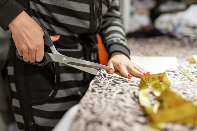 Een jonge meisjeontwerper van kleding, snijd stof per patroon om kleding te maken in zijn atelier