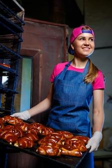 Een jonge meisjesbakker houdt een dienblad met warme gebakjes op de achtergrond van een industriële oven in een bakkerij. productie van bakkerijproducten.