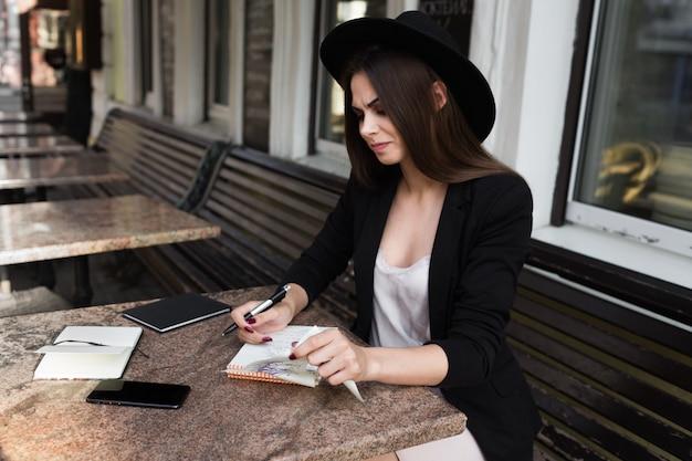 Een jonge meisjesschrijver schrijft artikelen voor een modeblad op een zomerveranda