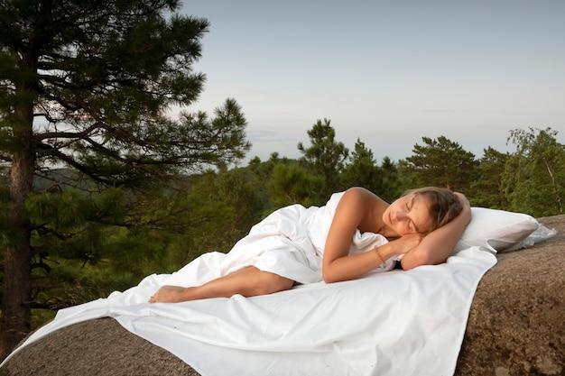 Een jonge meisjesvrouw slaapt op een wit laken in het bos op de rotsen van de schors in bed close-up sle...