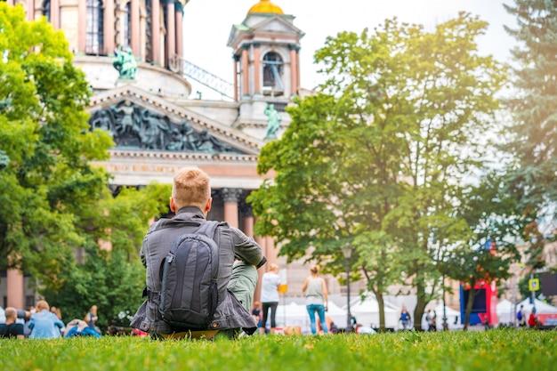 Een jonge mensentoerist met liggend op gras voor st. isaac kathedraal in saount petersburg