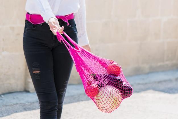 Een jonge moderne vrouw met aankopen. meisje draagt groenten en fruit in een milieuvriendelijke string, herbruikbare netzak. biologisch fruit in een netje