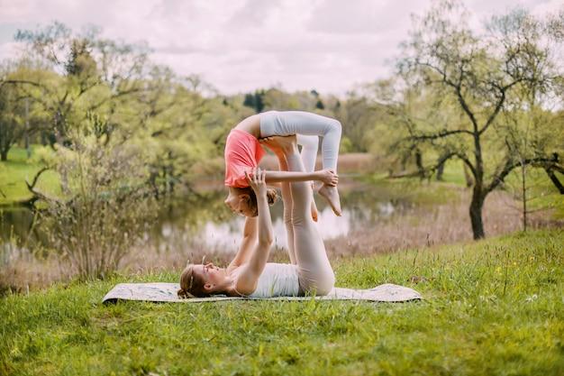 Een jonge moeder beoefent yoga met haar dochter.