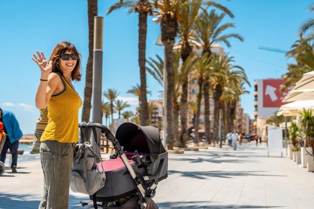 Een jonge moeder die haar baby in de auto laat lopen in de kustplaats torrevieja, alicante, valencia