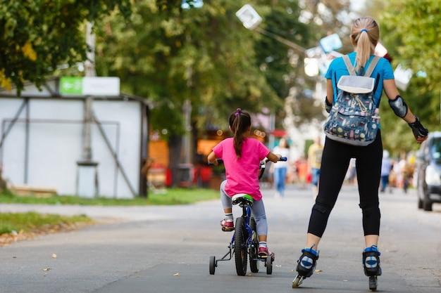 Een jonge moeder die rolschaatsen. dochter fietsen