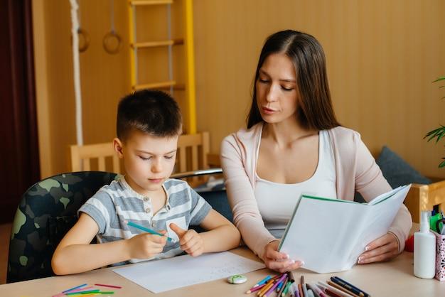 Een jonge moeder doet thuis huiswerk met haar zoon. ouders en training
