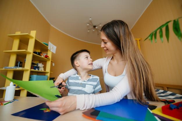 Een jonge moeder doet thuis huiswerk met haar zoon.
