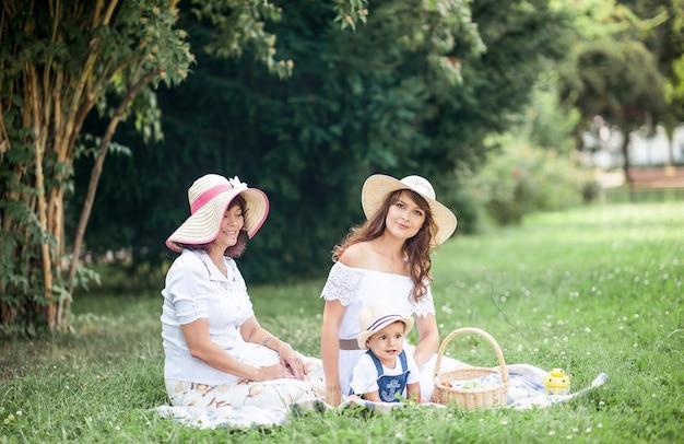 Een jonge moeder, een grootmoeder en een zoontje spelen op een open plek. picknick. voorjaar. zomer. warmte. de familie zit op het gras.