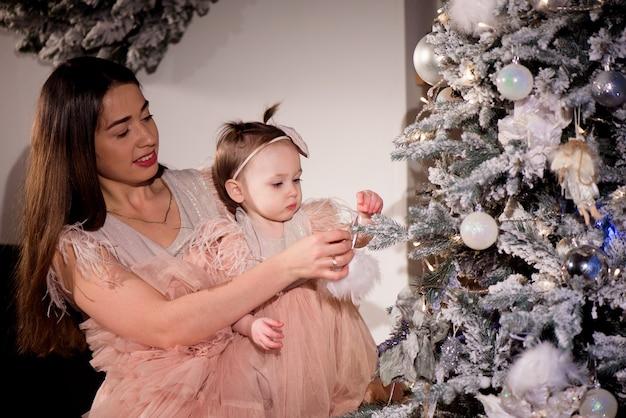 Een jonge moeder en dochter in bijpassende jurken versieren de kerstboom met nieuwe ballen