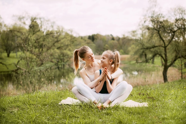 Een jonge moeder en dochter in sportkleding doen samen yoga in een park