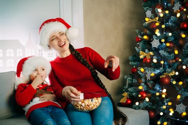 Een jonge moeder en haar dochter met kerstmutsen kijken thuis films voor kerstmis en eten popcorn